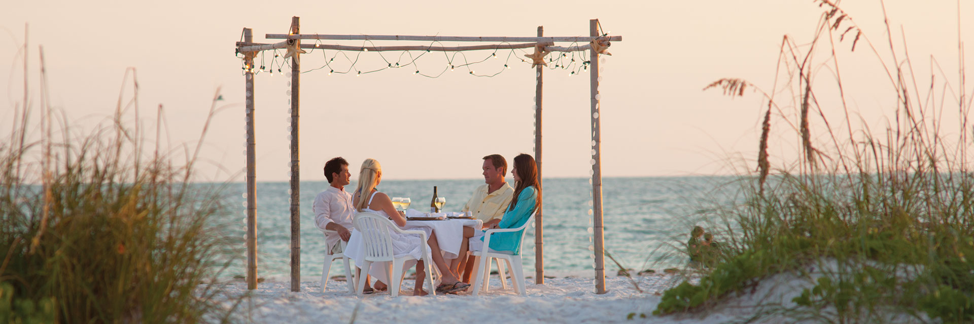 Two couples beach dining.