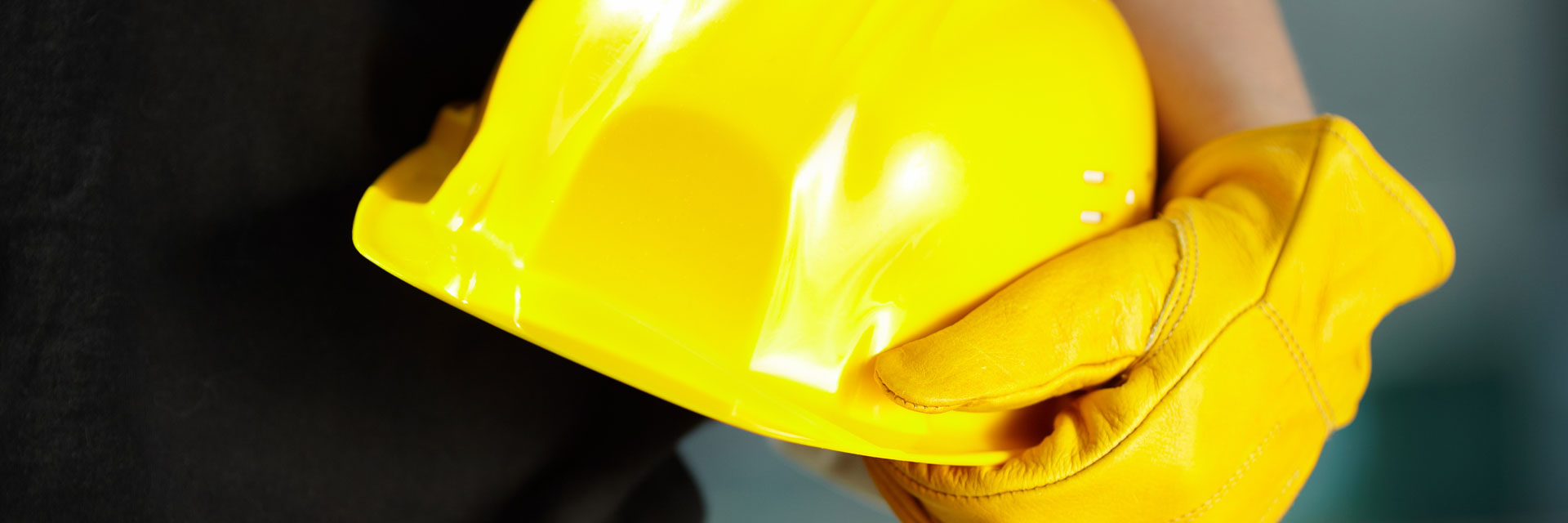Yellow hard hat and gloved hand.