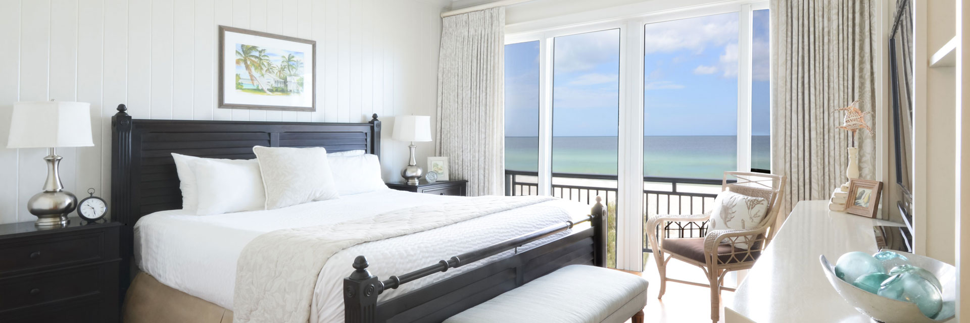 King bed in a resort room overlooking the beach.